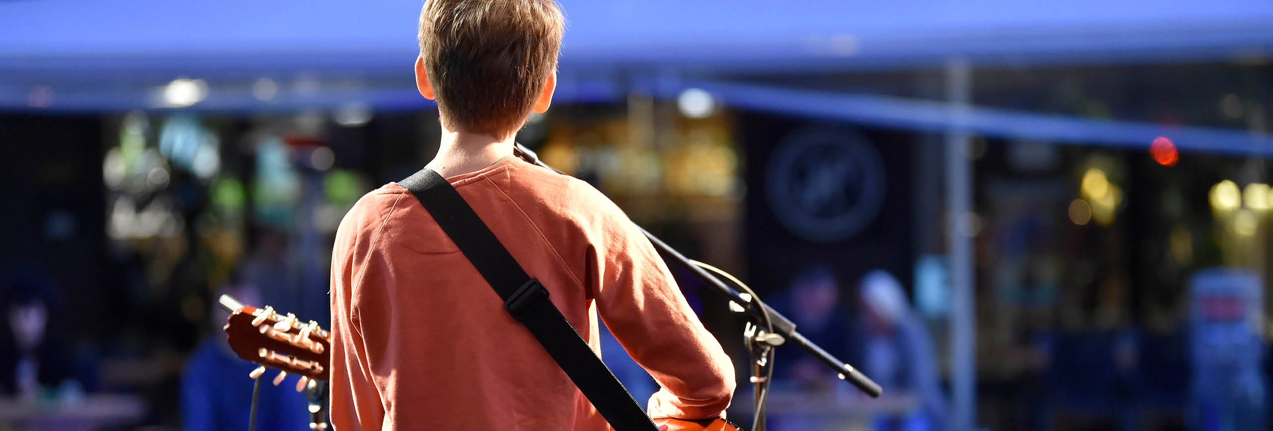 Boy playing guitar singing, from behind