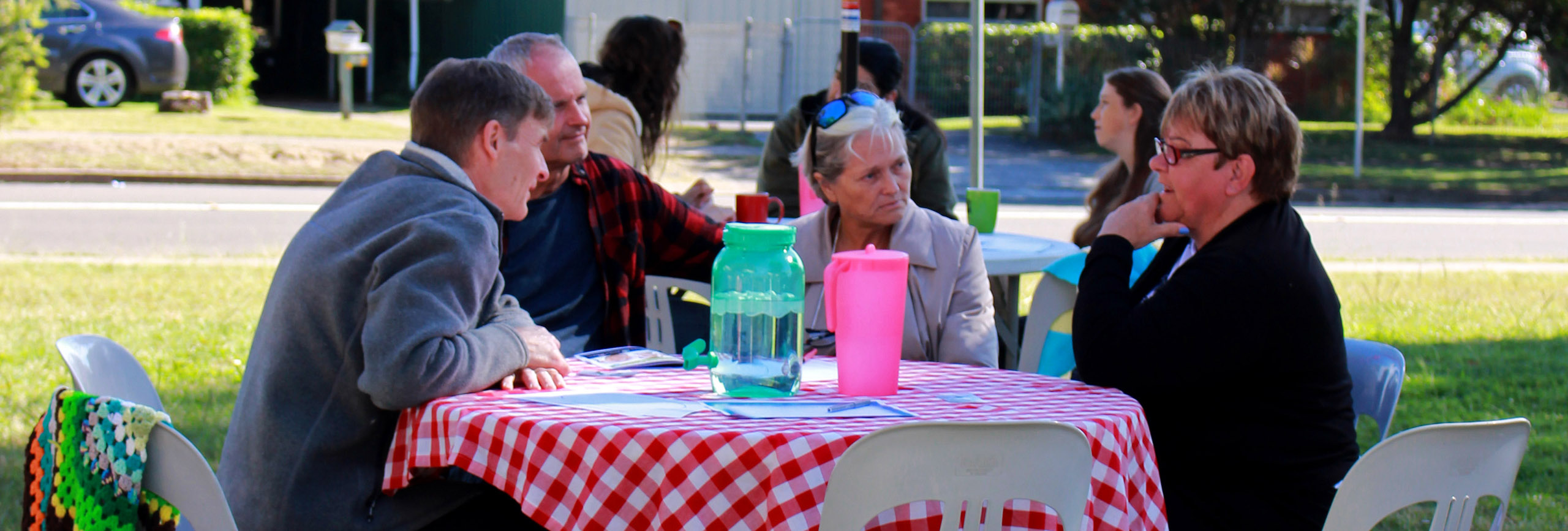 Group of people chatting at a table outdoors