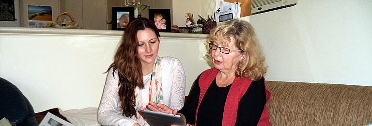 photo of Home Library Service volunteer sitting with a client on a home lounge looking at iPad