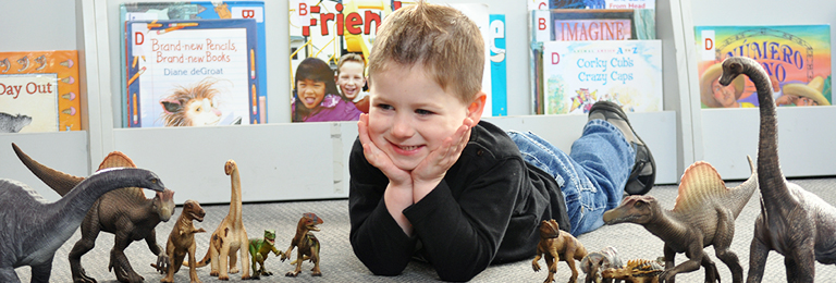 A boy using dinosaurs at Penrith Library's toy library